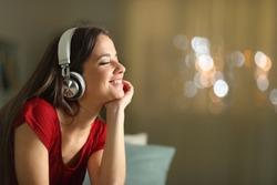 Happy woman wearing wireless headphones listening to music in the night sitting on a couch in the living room at home