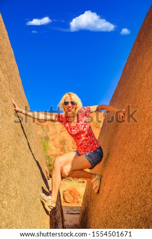 Happy woman wedged balancing between two naturally split boulder in Karlu Karlu, Northern Territory, Australian Outback at sunset. Devils Marbles are one of Australia's most famous natural wonders.