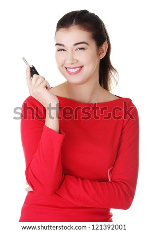 Happy woman with a car key. Isolated on white.