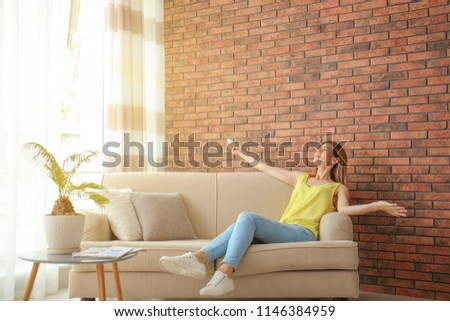 Happy woman with air conditioner remote at home #1146384959