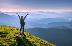 Happy woman with backpack and raised up arms on the peak and beautiful mountains in fog at sunset. Autumn landscape with sporty girl, green grass, forest, hills , blue sky in fall. Travel and tourism
