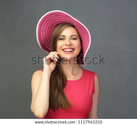 Happy woman with big toothy smile wearing red hat and dress. Portrait on gray background.