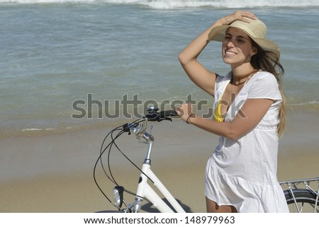 happy woman with bike on the beach wearing bikini