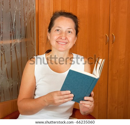 Happy woman with blue book sitting and smiling