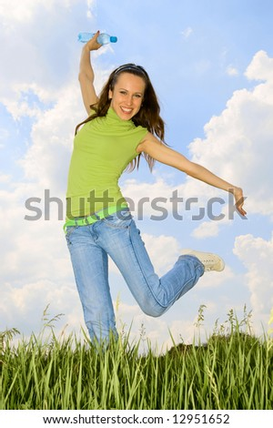 happy woman with bottle against blue sky