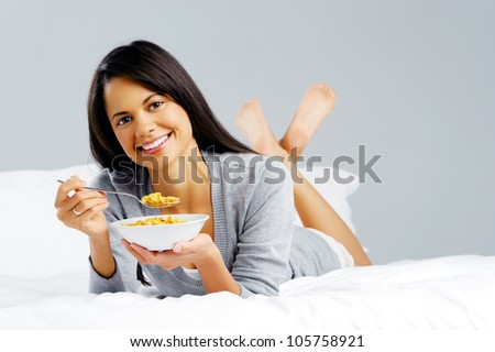 Happy woman with bowl of cornflakes eating breakfast in bed. healthy start to the day