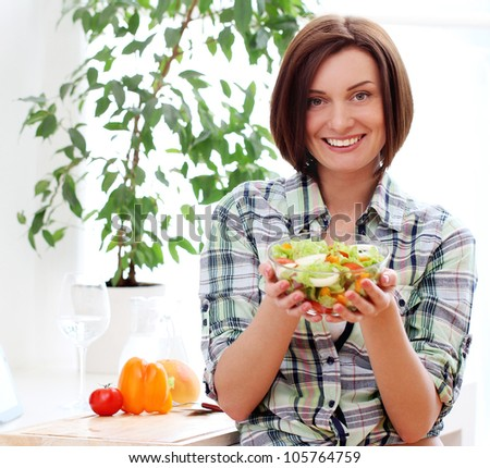 Happy woman with bowl of fresh and healthy salad