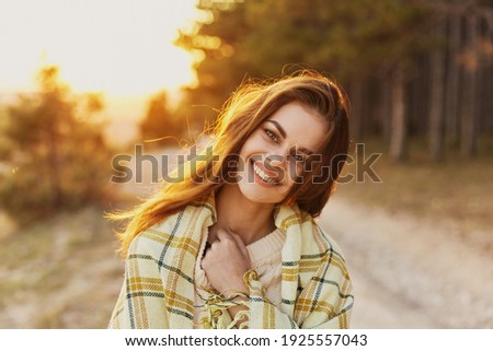 Happy woman with bread on her shoulders laughs front view and sunset in the background