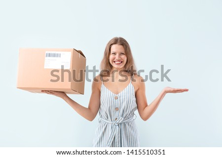 Happy woman with cardboard box on light background