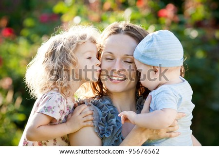 Happy woman with child and baby outdoors in spring garden