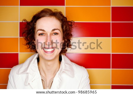 Happy woman with colorful tiles in the background