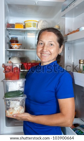 Happy woman with containers of vegetables near the fridge at home