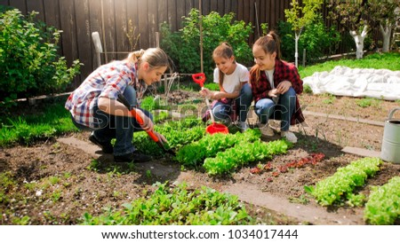 Happy woman with daughters planting seeds in garden #1034017444