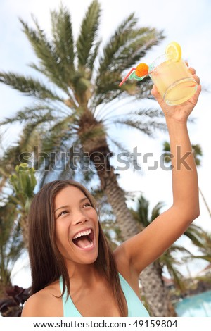 Happy woman with drink at tropical resort toasting. Beautiful mixed race caucasian / chinese young woman model having fun saying cheers.