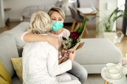 Happy woman with face mask embracing senior mother while bringing flowers and visiting her at home during coronavirus epidemic.