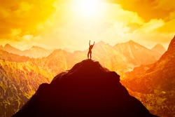 Happy woman with hands up on the peak of the mountain enjoying the success, freedom and bright future.