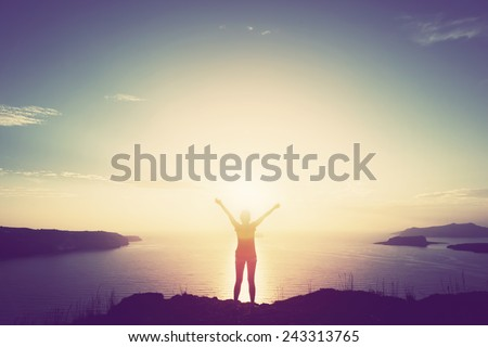 Happy woman with hands up standing on cliff over sea and islands at sunset. Vintage mood, concepts of winner, freedom, happiness etc.