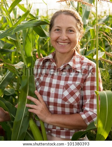 Happy woman with harvest of corn in  field