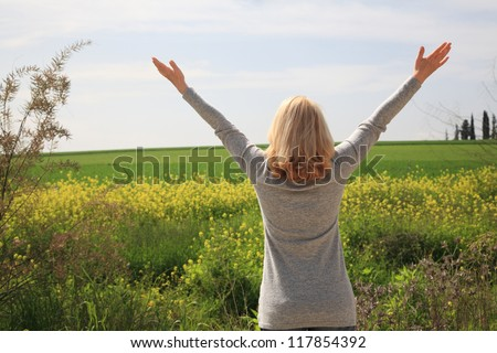 Happy woman with her arms wide spread is enjoying in the sunny day and surrounding nature.