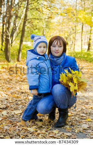Happy woman with her son in autumn park