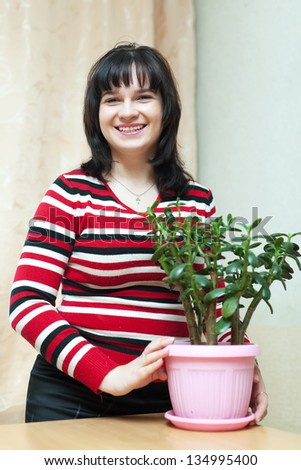 Happy woman with  jade in flowering pot in  room