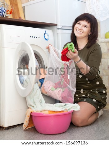 Happy woman with laundry bag  near washing machine