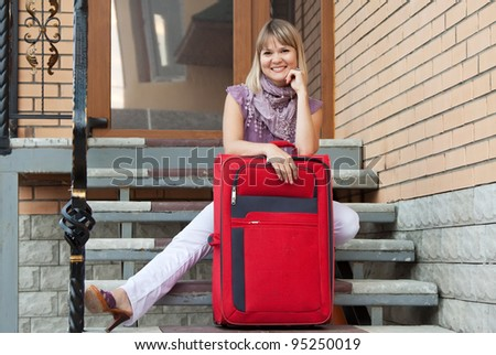 Happy woman with luggage sitting near home door