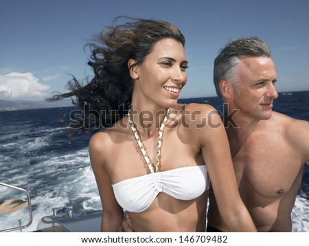 Happy woman with man looking away on yacht