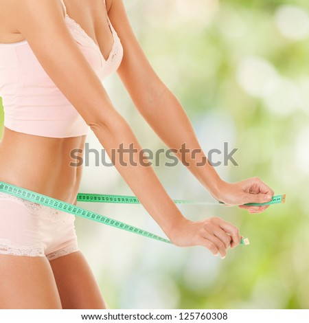 happy woman with measure tape on nature background