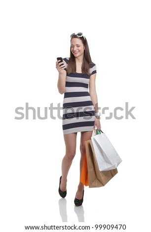 Happy woman with mobile phone and shopping bags