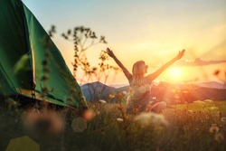 Happy woman with open arms stay near tent around mountains under sunset light sky enjoying the  leisure and freedom.