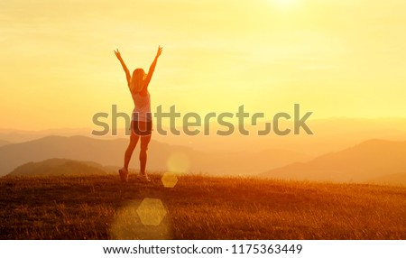Happy woman with open arms stay on the peak of the mountain cliff edge under sunset light sky enjoying the success, freedom and bright future. #1175363449