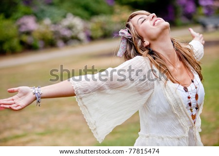 Happy woman with opened arms outdoors enjoy her freedom