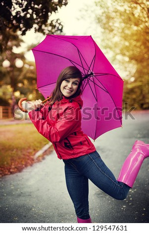 Happy woman with pink umbrella and rubber boots