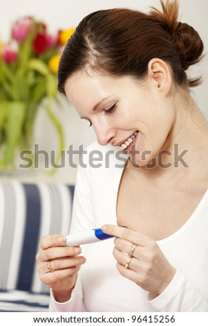 Happy woman with positive pregnancy test