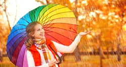 happy woman with rainbow multicolored umbrella under rain on nature in the park
