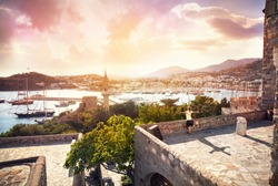 Happy Woman with rising hands on the Bodrum Castle near Aegean Sea with yachts at sunset
