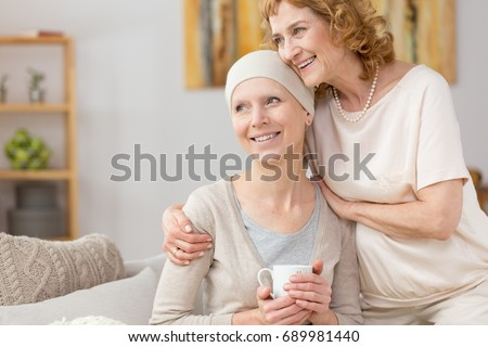 Happy woman with scarf struggling with illness with her mom's help