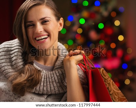 Happy woman with shopping bag in front of Christmas lights
