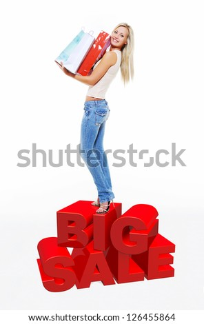 Happy woman with shopping bags isolated on white. Girl standing on 3 dimensional text. - Shutterstock ID 126455864