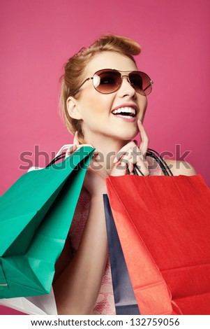 Happy woman with shopping bags screaming. Isolated on pink