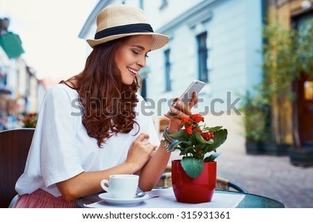 Happy woman with smartphone in outdoor cafe #315931361