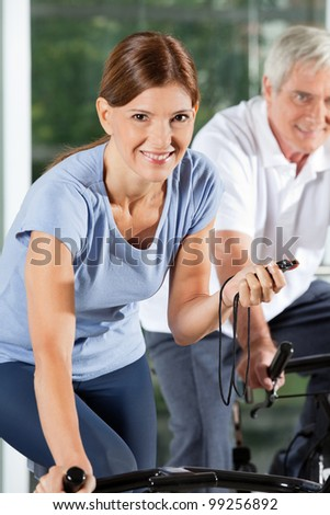 Happy woman with stopwatch in gym on bike