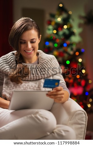Happy woman with tablet PC and credit card in front of Christmas tree