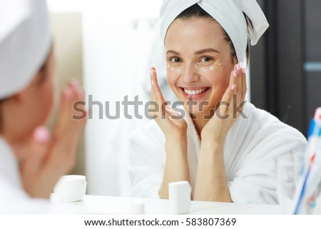 Happy woman with toothy smile pampering eye-cream