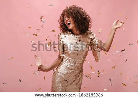 Happy woman with wavy dark hair style in shiny trendy clothes rejoicing, holding glass with champagne and posing with confetti on pink backdrop..