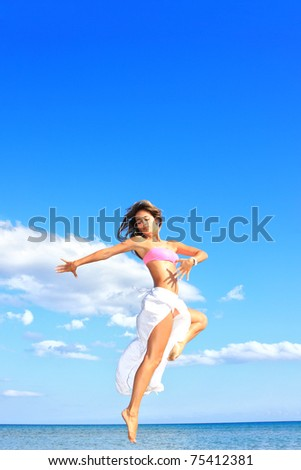 happy woman with white sarong relaxing on the beach