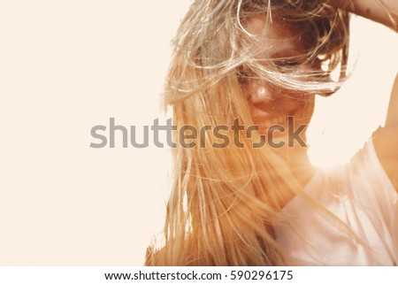 Happy woman with windy messy hair backlit by sun selective focus colorized image, copy space.