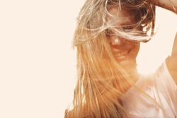 Happy woman with windy messy hair backlit by sun selective focus colorized image, copy space. Jolly girl windswept hair full of sunshine glow.