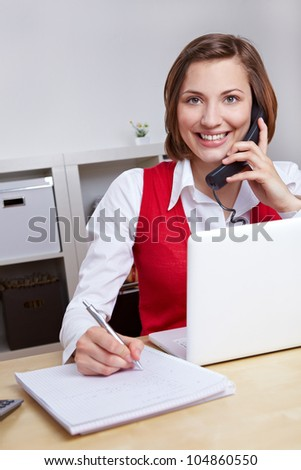 Happy woman working for call center hotline taking notes during a phone call